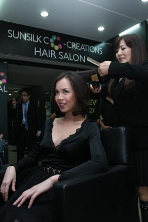 Bà Yuko sử dụng chính phát minh của mình – máy kẹp tóc để giúp Ngọc Oanh trở nên quyến rũ hơn với kiểu tóc mới.