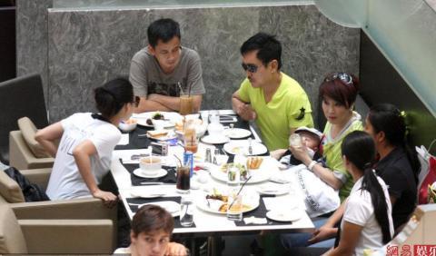 Cả gia đình ngồi trong nhà hàng của khu trung tâm thương mại, dùng bữa ăn nhẹ với bánh mỳ, mỳ và trà.