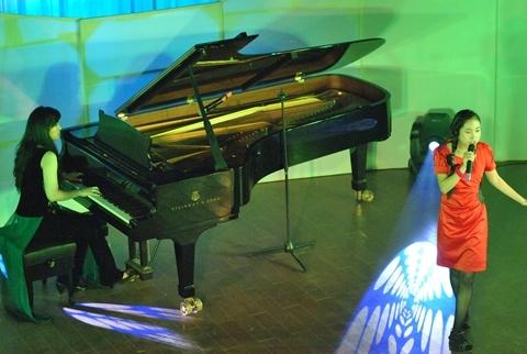 Thùy Dung đệm đàn piano cho học sinh hát trong đêm biểu diễn nghệ thuật kỷ niệm một năm ngày thành lập Seedlink hôm 23/4.