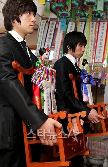 Hai người họ hàng bê hình nộm của cô dâu chú rể khi làm lễ.