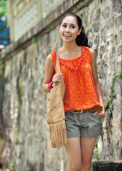 Nữ diễn viên truyền hình vận áo dây, quần short, khoác túi vải dạo chơi công viên. Hình ảnh trẻ trung của cô được thể hiện qua ống kính nhiếp ảnh gia Lý Võ Phú Hưng.