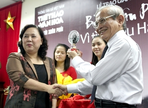 Giáo sư Phan Huy Lê và kỷ niệm chương có hình họa sĩ Bùi Xuân Phái.