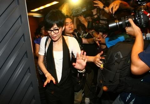 Vương Phi né tránh khi các phóng viên không ngừng chụp ảnh cô.