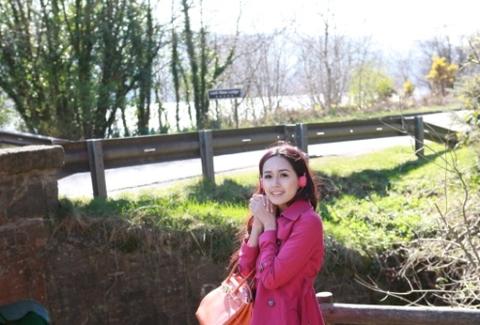 Mai Phương Thúy diện chiếc áo choàng màu hồng tím trẻ trung, đeo tai nghe cùng tông màu
