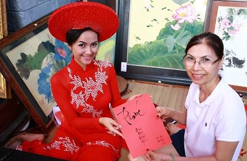 Ngọc Hân diện áo dài khăn đóng tại lớp học thư pháp do cô chủ trì.
