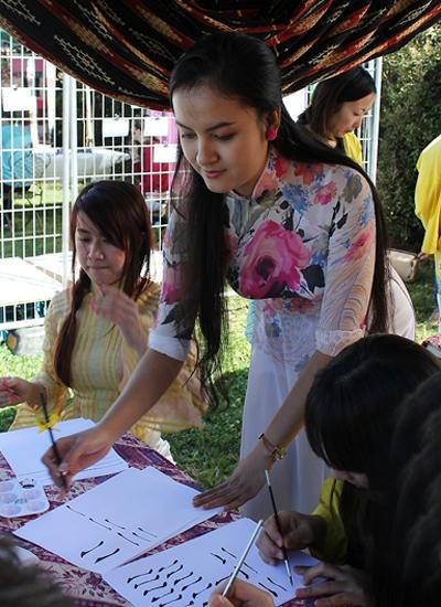 Ngọc Hân tận tình chỉ dạy các học sinh cách viết thư pháp.