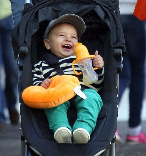 Cậu con trai của siêu mẫu với tài tử Orlando Bloom cười ngoác miệng khi đi dạo. Trên tay Flynn ôm chặt bình sữa.