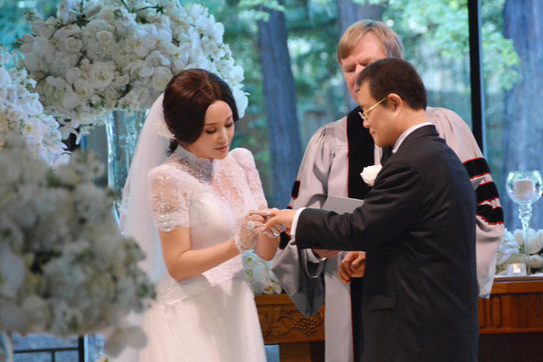 """Phút trao nhau nhẫn cưới. Vương Hiểu Ngọc theo đuổi Lưu Hiểu Khánh khoảng 20 năm, cuối cùng ông cũng cưới được người trong mộng, dù đã ở tuổi thất tuần. Doanh nhân nói trong đám cưới: """"Hiểu Khánh, Livia (tên thân mật Hiểu Ngọc gọi Hiểu Khánh) thân yêu của tôi, bao nhiêu năm trời ngưỡng mộ và chờ đợi, cuối cùng hôm nay được nắm tay em, được cùng em bước vào nơi thiêng liêng này. Từ nay về sau, tôi sẽ tôn trọng em, chăm sóc em, mãi mãi yêu em thật nồng nàn. Dù con đường phía trước chông gai thế nào, tôi đều là chồng em. Nếu con người ta bất tử nơi Thiên quốc, tôi muốn người mãi mãi bên tôi là em, Livia  người tôi yêu sâu đậm."""