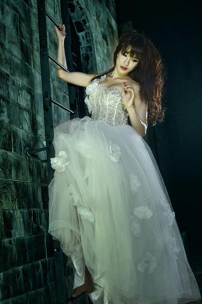 Đầu tiên là chiếc váy cưới phồng xòe bồng bềnh như 1 nàng công chúa lạc trong lâu đài,  với chi tiết voan lưới kết hợp  đính hạt pha lê tinh xảo ở phần cúp ngực. Kiểu tóc thập niên 60 với mái phồng duyên dáng cùng sợi ruy băng thắt nơ, cô dâu trông ngọt ngào nữ tính.