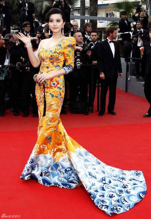 """Trong khi đó, phom dáng phần đuôi váy của Phương Trinh lại được cho là đã mượn ý tưởng từ bộ """"Long bào"""" nổi tiếng của Phạm Băng Băng trên thảm đỏ Cannes 63. Có thể thấy, người đẹp đã cắt ghép từ hai bộ váy để tạo thành một thiết kế của riêng mình."""