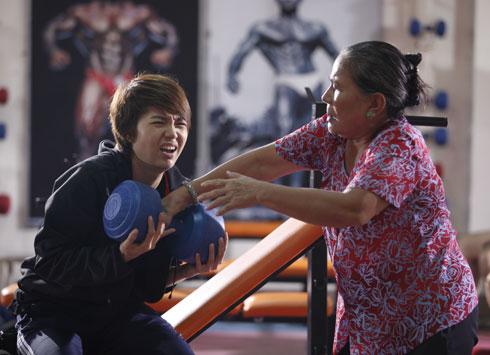 Nghệ sĩ Ưu tú Lê Thiện (phải) vào vai bà nội cổ hủ của Đông Dương. Bà rất thương cháu nhưng rất bực bội và thất vọng khi cháu của mình không khỏe mạnh, cơ bắp như các đấng nam nhi khác nên quyết bắt cháu đi tập tạ. Diễn xuất của
