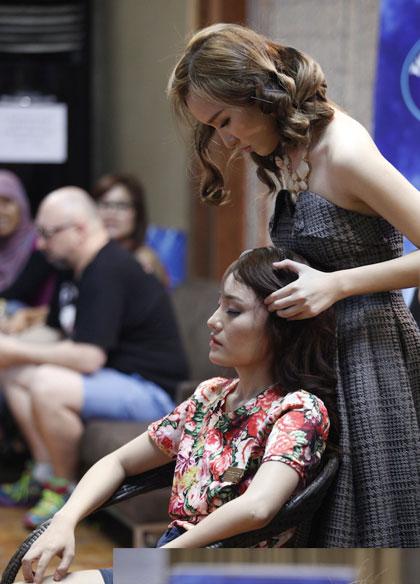 MC hậu trường Thảo My xoa bóp đầu cho thí sinh Nhật Thủy khi cô cảm thấy căng thẳng.