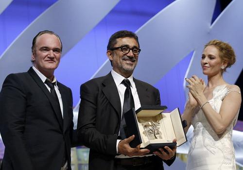 Đạo diễn Nuri Bilge Ceylan (giữa) nhận Cành Cọ Vàng từ đạo diễn Quentin Tarantino và minh tinh Uma Thurman trong đêm bế mạc LHP Cannes 2014 tối 25/5. Ảnh: AFP.