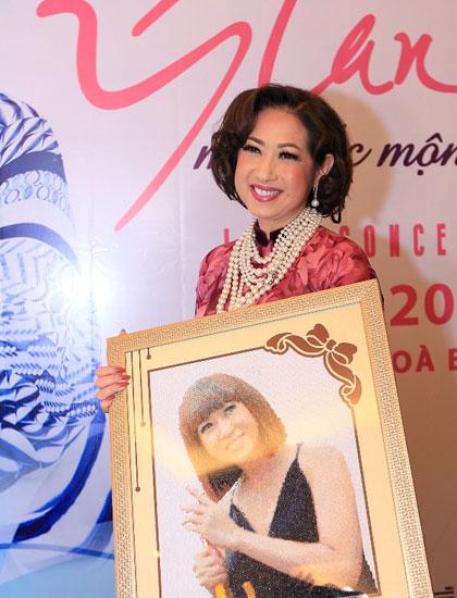 Ý Lan bên bức tranh thuê do trẻ em mồ côi tặng chị tại buổi họp.