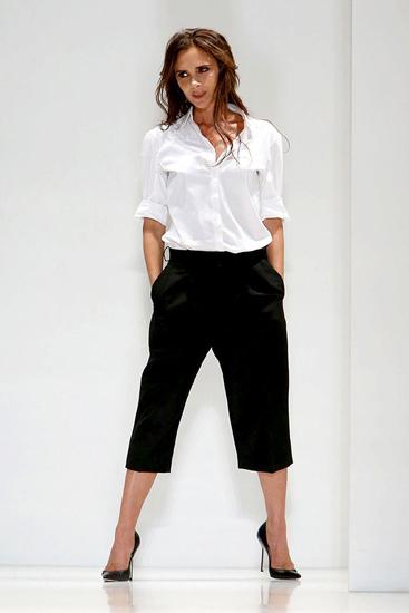 Với phong cách menswear trên trang phục tối giản, Victoria Beckham xuất hiện đầy cá tính  nhưng vẫn thanh lịch cùng áo sơ mi trắng và quần lửng culottes.