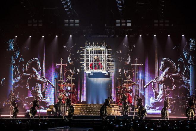 Madonna đứng hát trong lồng sắt treo lơ lửng giữa không trung