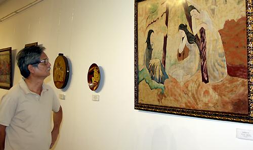 Nhà sưu tập Nguyễn Trọng Chức đang xem bức họa được đề tên