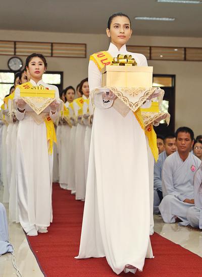 Là mỹ nhân ăn chay trường, lại thành tâm hướng Phật, chính vì vậy mà Á hậu Trương Thị May được lựa chọn dẫn đầu 100 bạn mặc áo dài trắng, trên ngực cài bông hồng đỏ bước vào Chánh điện chùa Hoằng Pháp thực hiện nghi lễ cài hoa, dâng y cho trụ trì và các chư tăng tại đây