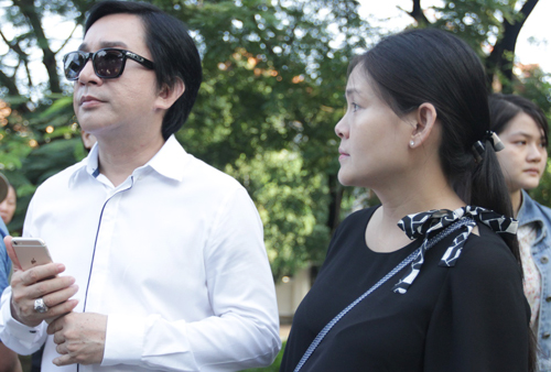 Trinh Trinh mang bầu đứng nép vào người chồng - NSƯT Kim Tử Long trong đám tang.