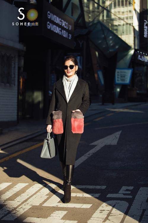 Chi tiết túi áo với chất liệu lông tổng hợp là điểm nhấn thú vị giúp mẫu áo khoác dạ màu đen trở nên bắt mắt và sành điệu hơn.