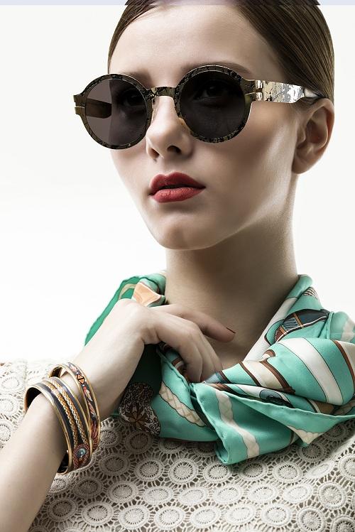 Mẫu kính hi - fashion với mắt kính phẳng màu đen, họa tiết vân đá được thực hiện bởi công nghệ cắt laser tiên tiến. Hi - fashion mang phong cách avant  garde, mẫu thiết kế kết hợp của Mykita và Maison Margiela là gợi ý cho set đồ đón Tết của những cô nàng có cá tính mạnh. MMTransfer 003 có giá 24,4 triệu đồng.