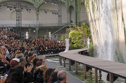 1. Gần đây nhất, hôm 3/10, nhà thiết kế Karl Lagerfeld đã cho dựng một thác nước khổng lồ với cảnh quan thiên nhiên trông như thật ngay bên trong bảo tàng Grand Palais nhằm phục vụ cho show diễn Chanel ready-to-wear Xuân Hè 2018. Các người mẫu catwalk trên cây cầu gỗ bao quanh ngọn thác nhân tạo.