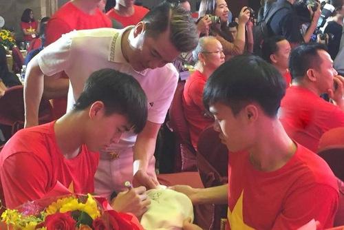 Trước khi biểu diễn, Đàm Vĩnh Hưng tranh thủ đi xin chữ ký từng thành viên trong đội lên chiếc áo vest của mình.