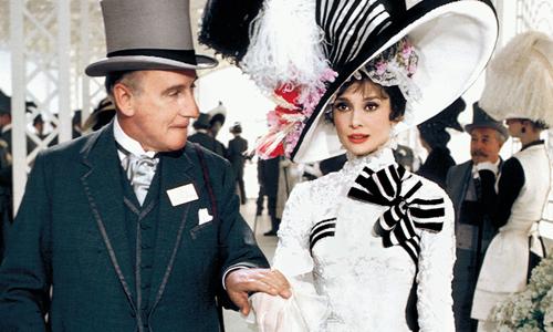 Nhân vật giáo sư Henry Higgins (trái) đưa Eliza Dootlittle tham gia buổi khiêu vũ.