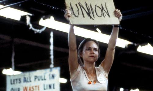 Nhân vật Norma Rae đứng lên bàn và giơ cao bảng hiệu trong cuộc biểu tình.