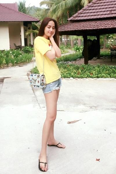 Mẫu túiLouis Vuitton dây xíchhọa tiết trẻ trung được cô kết hợp cùng áo thun, quần sort khi đi biển.