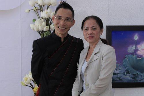 Họa sĩ Trần Huy Khuê (trái) cùng khán giả trong buổi triển lãm.