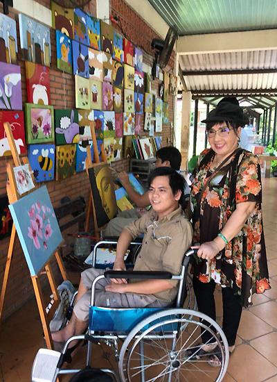 Lệ Thủy bên một họa sĩ trẻ chuyên vẽ tranh phong cảnh.
