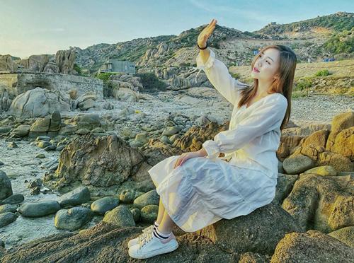 Quỳnh Kool mặc váy suông, kết hợp với giày thể thao đồng màu khi đi du lịch.