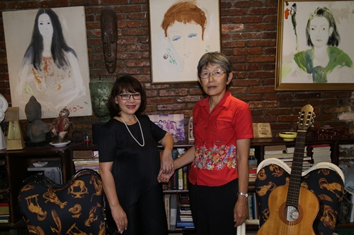 Michiko Yoshii bên ca sĩ Trịnh Vĩnh Trinh ở nhà riêng của Trịnh Công Sơn năm 2018. Trên tường treo bức tranh cố nhạc sĩ từng vẽ bà (giữa).