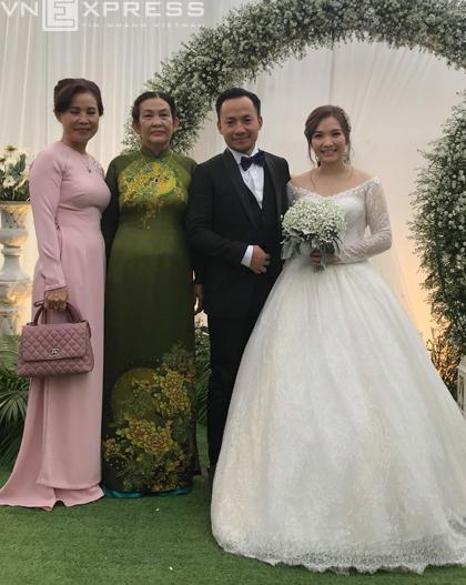Mẹ cô dâu (áo dài xanh) đứng tiếp khách. Buổi tiệc tổ chức ngoài trời, trang trí theo tông trắng với hoa hồng, đồng tiền. Khoảng 700 khách mời dự tiệc ở Bình Thuận.