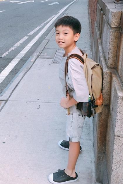 Nhóc tỳ chuộnggu thời trang giản dị với giày sneakers, sơmi và quần short.