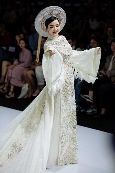 Sở hữu vóc dáng chuẩn mực, kết hợp với vẻ đẹp kiêu sa, Hoa hậu Đền Hùng Giáng My trở thành sự lựa chọn mở màn của nhà thiết kế Lê Long Dũng. Khoác lên mình trang phục áo dài trắng được đính kết những hột đá, pha lê lấp lánh cộng hưởng phần tà có chiều dài