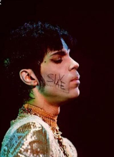 Ca sĩ Prince viết chữ Slave (tạm dịch: nô lệ) trên mặt để phản đối hãng đĩa sở hữu bản quyền thu âm gốc của ông. Ảnh: The Guardian.