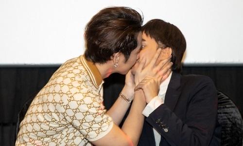 Tuấn Trần (trái) hôn Hương Giang ở sự kiện. Ảnh: CGV.