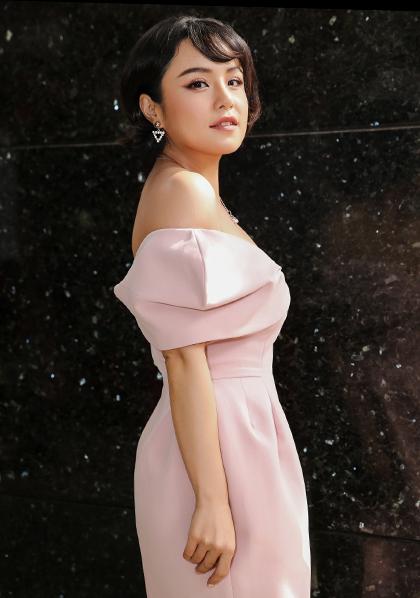 Ca sĩ Thái Trinh tạo dáng với bộ đầm trễ vai. Gần đây, cô đeo đuổi phong cách gợi cảm.